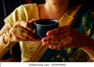 woman indian hold cup tea masala national smile.Female hands decoratively colored by henna with coffee mug