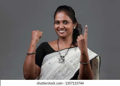 A woman of Indian origin shows her finger marked with ink after casting vote.