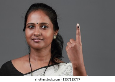 A woman of Indian origin shows her finger marked with ink after casting vote. Selectively focused on the finger.