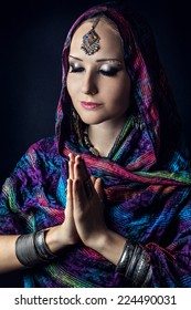 Woman with Indian tikka wrapped in scarf doing Namaste mudra at dark background