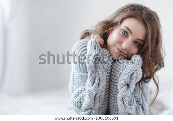女性の室内用ポートレート。家で温かい編み物を着た若い美人。ファッション。秋冬