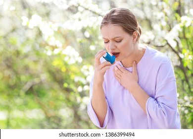 Woman with inhaler having asthma attack on spring day