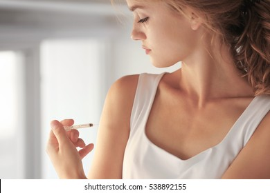 Woman injecting hand at home