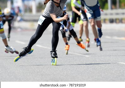 A woman is inline skating with a smartphone.