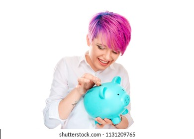 Woman inserting coin in a piggy bank isolated on white background. Millennial model with pink magenta hair. Saving concept