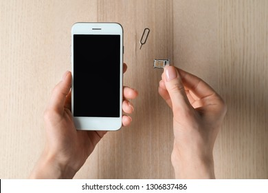 Woman inserting sim card into mobile phone, top view