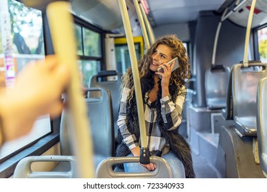 Woman inside a bus  on the phone .Young Woman Typing On Her Smart Phone In Public Transportation.