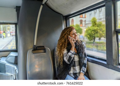Woman inside a bus  on the phone.Young woman is on the phone while commuting