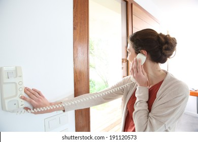 Woman inside home answering security phone