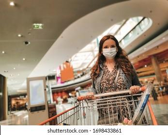 Frauen in einem Einkaufszentrum mit medizinischer Gesichtsmaske zum Schutz des COVID-19-Virus