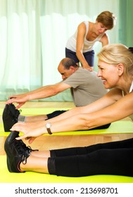 Woman instructor helping senior people to stretch