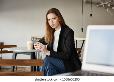 Woman is insulter with offensive words of stranger sitting with laptop. Portrait of annoyed attractive woman in cafe, holding smartphone and drinking coffee, frowning at person who tells rude things