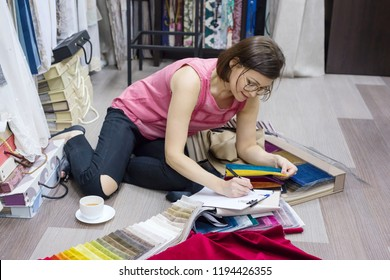 Woman interior designer, works with samples of fabrics for curtains and blinds. Business - textile industry