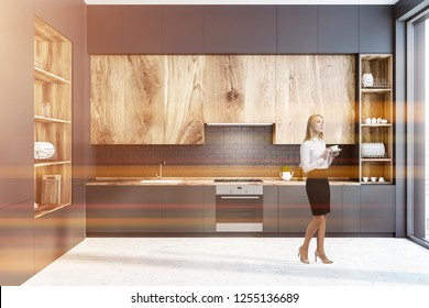 Woman in interior of modern kitchen with black brick walls, concrete floor, gray countertops and wooden cupboards and big gray and wooden cupboard on the left. Toned image