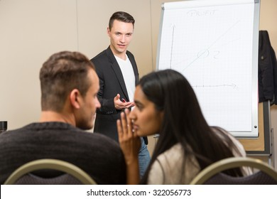 Woman interrupting speaker with flip chart giving a lecture
