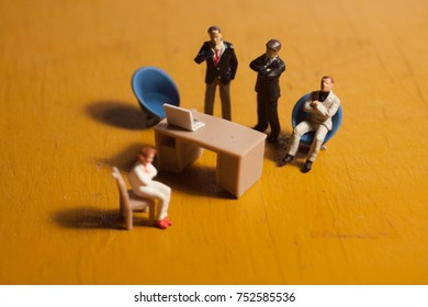 Woman is interviewed by an intimidating group of business men. Concept of sexual harassment, intimidation, gender inequality or isolation. Depicted in miniature. Employee being fired or dismissed.
