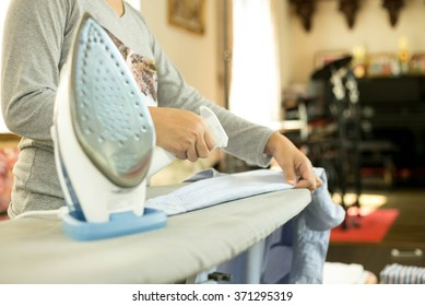 Woman ironing a blue shirt with a steam iron in blur background
