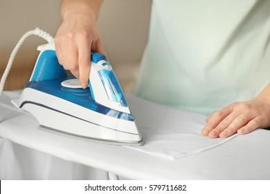 Woman ironing cloth on board, closeup
