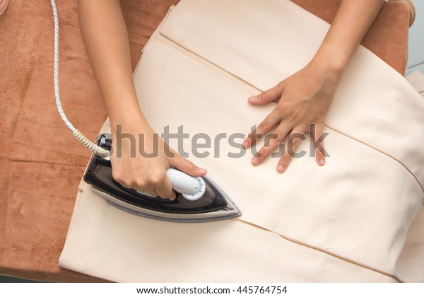Woman ironing clothes on ironing board