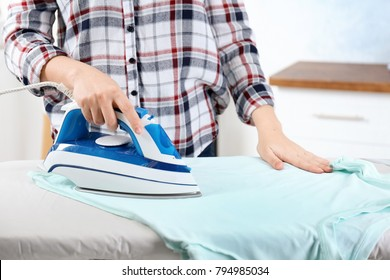 Woman ironing laundry, indoors
