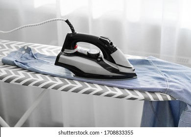 woman ironing men's blue shirt on an ironing board. Macro