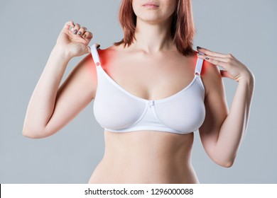 Woman with irritated skin under bra, irritation on the body from underwear on gray background, painful area highlighted in red
