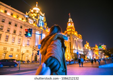 Woman in jacket clothes leading man to the bund in shanghai. Traveling together. Follow me.