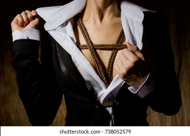 A woman in a jacket under which is hidden the harness Shinju made in the Japanese technique, shibari