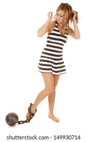 A woman in a jail outfit with a ball and chain on his foot.
