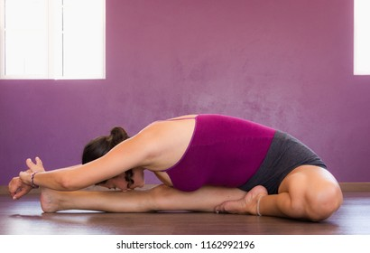 Woman in janu sirsasana on wood planks floor studio. Female yogi on head to knee forward bend over purple wall. Lady practices yoga. Sitting posture, spinal twist, stretching concepts