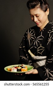Woman in Japanese costume, holding plate of Japanese food