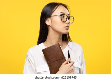 Woman japanese in glasses on an orange background with notepad in hands work office business