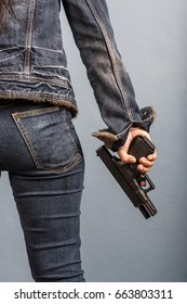 Woman in jeans is holding a gun in her hand.