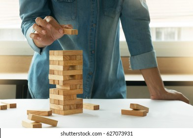 Woman in jeans shirt holding blocks wood game