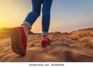 Woman jeans and sneaker Red Color shoes Walking on stone Wall