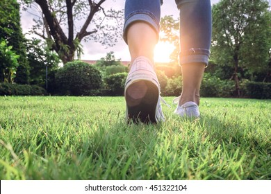 Woman jeans and sneaker shoes on Sunset walking in garden
