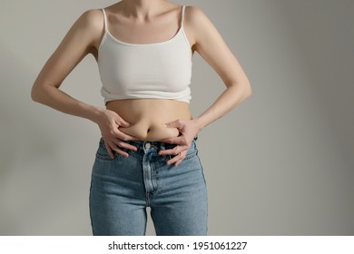 Frauen in Jeans und weißes Hemd, die ihren Bauch fett drücken. Weibliche Hüften, Nahaufnahme eines rohen Studios auf grauem Hintergrund. Diät und Fettverlust Konzept.