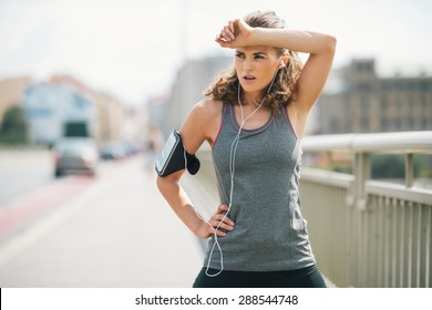 A woman jogger is taking a break, wiping sweat from her forehead with her forearm. She's taking a moment to catch her breath before getting down to the beat of her music and continuing her power run.