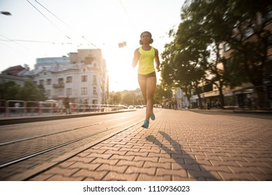 Woman jogging along the street, sun in background.