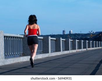 Woman jogging at the bridge. Back view