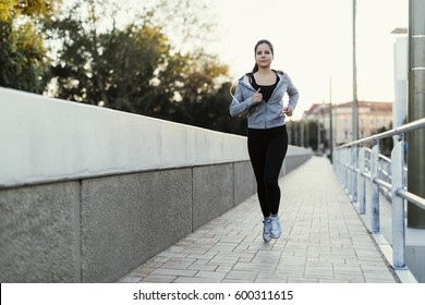 Woman jogging in city and keeping her body in shape