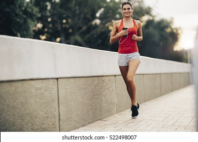 Woman jogging in city and listening to music while sun is about to set