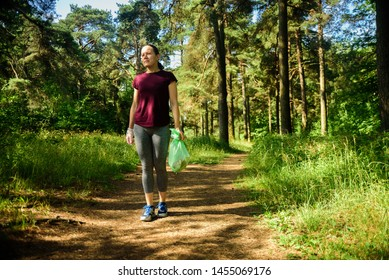 Woman jogging with garbage bag in forest. Collecting trash. Plogging concept