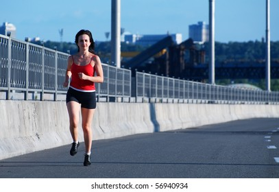 Woman jogging at the highway, front view