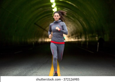 Woman jogging on run through city downtown tunnel street lights tough conviction fitness
