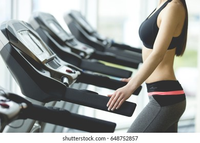 The woman jogging on the treadmill in the gym