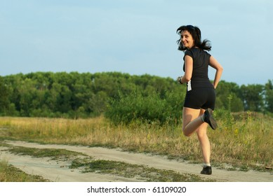Woman jogging outdoors on the meadow turn around