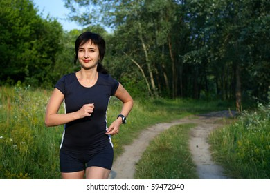 Woman jogging outdoors in summer forest