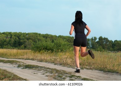 Woman jogging outdoors in summer meadow