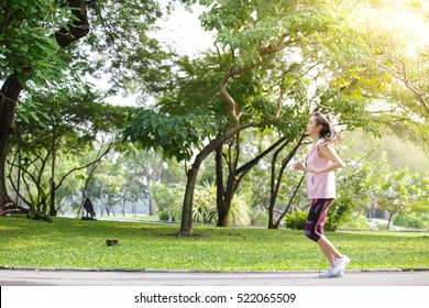 Woman jogging at park in sunrise light.